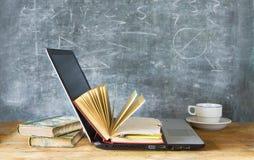 Apra il libro ed il computer portatile fotografia stock