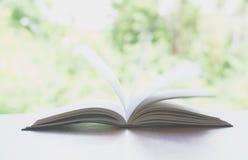 Apra il libro Prenoti, aperto, sulla vecchia tavola di legno sulla natura Fotografia Stock