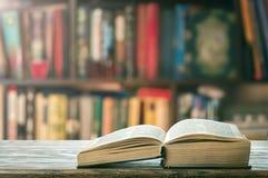 Apra il libro spesso sullo scaffale per libri Immagine Stock