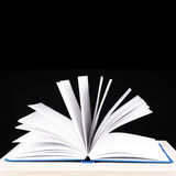 Apra il libro su una priorità bassa nera Fotografia Stock Libera da Diritti