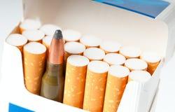 Apra il pacchetto delle sigarette con una cartuccia dell'arma Immagini Stock