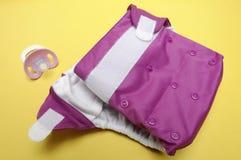 Apra il pannolino del panno con il manichino su priorità bassa gialla Fotografie Stock