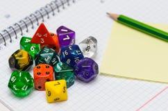Apra il quaderno con la carta, la matita appiccicosa ed il gioco di ruolo dic Fotografie Stock