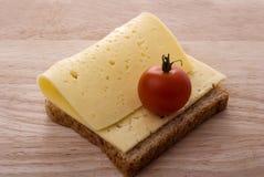 Apra il sandwich del formaggio con il pomodoro sul tagliere di legno Fotografia Stock Libera da Diritti