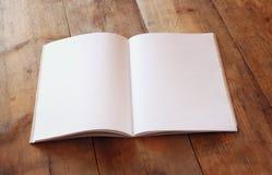 Apra il taccuino in bianco sopra la tavola di legno aspetti per il modello retro immagine filtrata Immagine Stock