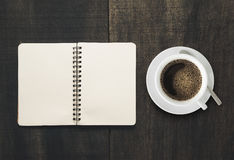 Apra il taccuino con la tazza di caffè sullo scrittorio di legno nero pagina Empt Fotografia Stock