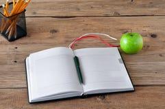 Apra il taccuino con le pagine in bianco, la penna e la mela verde Immagini Stock