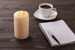 Apra il taccuino con le pagine in bianco, la penna, il caffè, candela bruciante Fotografie Stock