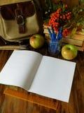 Apra il taccuino di carta con i rifornimenti e le mele di scuola nei precedenti Fotografia Stock Libera da Diritti