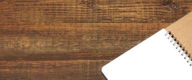 Apra il taccuino diretto a spirale con i white pages su fondo di legno Fotografia Stock