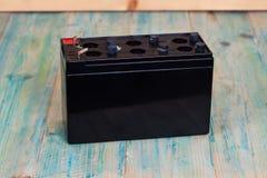 Apra la batteria sigillata su fondo di legno Fotografia Stock