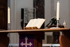 Apra la bibbia e le candele sull'altare di una chiesa Fotografia Stock