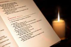 Apra la bibbia e una candela nello scuro Immagine Stock Libera da Diritti