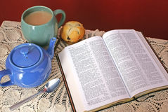 Apra la bibbia sulla tavola con la tovaglia d'annata, la teiera, la tazza e la MU fotografia stock libera da diritti