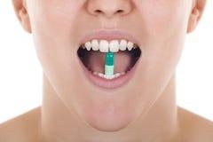 Apra la bocca con la pillola fra i denti Immagine Stock