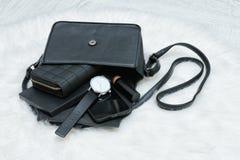 Apra la borsa nera con le cose cadute, il taccuino, il telefono cellulare, watc Fotografia Stock