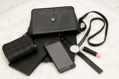 Apra la borsa nera con le cose, il telefono cellulare, l'orologio, la borsa ed il rossetto caduti La pelliccia bianca su fondo, v Fotografia Stock
