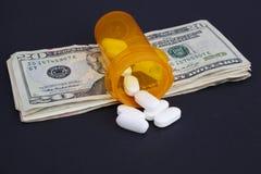 Apra la bottiglia di pillola di prescrizione su una pila di soldi fotografia stock