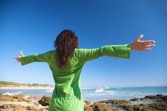 Apra la donna del vestito da verde delle braccia Immagine Stock