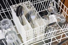 Apra la lavastoviglie con i cucchiai, le forchette ed i vetri Fotografia Stock Libera da Diritti