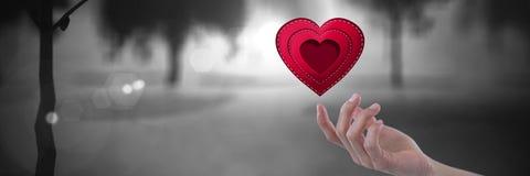 apra la mano che tocca un cuore cucito con gli alberi misteriosi romantici Immagine Stock