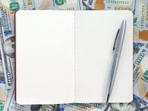 Apra la nota con la penna sulle banconote del dollaro Modello e fondo Immagine Stock Libera da Diritti