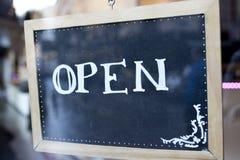 Apra la parola scritta su una piccola lavagna Fotografie Stock