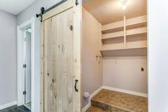 Apra la porta di granaio ad una piccola stanza di lavanderia fotografia stock libera da diritti