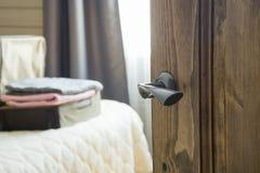 Apra la porta di legno ed osservi alla camera da letto Apra la valigia con i vestiti sul letto Fotografia Stock