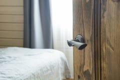 Apra la porta di legno ed osservi alla camera da letto ed al letto Priorità bassa vaga Immagine Stock