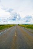 Apra la strada sotto un cielo nuvoloso fra i giacimenti del girasole Fotografia Stock