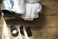 Apra la valigia con i vestiti femminili per il viaggio sul pavimento di legno Fotografia Stock Libera da Diritti