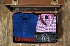 Apra la valigia di viaggio con i vestiti casuali dell'uomo Immagini Stock Libere da Diritti