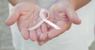 Apra le mani che tengono il nastro di consapevolezza del cancro al seno archivi video
