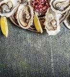 Apra le ostriche in piatto con il limone e gli scalogni sauce su fondo rustico, vista superiore Immagine Stock