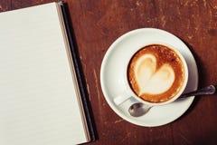 Apra un taccuino e una tazza di caffè bianchi in bianco Fotografia Stock Libera da Diritti