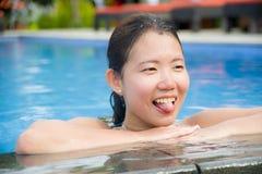 apreciação asiática feliz e consideravelmente chinesa nova da mulher alegre e relaxado tendo o divertimento que sorri na piscina  Imagem de Stock