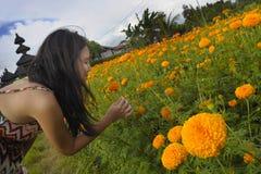 A apreciação chinesa asiática nova da mulher do turista relaxado o cheiro da vista e do perfume de um campo de flores bonito ajar Fotografia de Stock