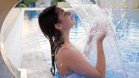 Apreciação da jovem mulher sob a cachoeira de refrescamento na piscina fora no resto do verão vídeos de arquivo