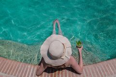 Apreciação fêmea na piscina e guardar o cocktail do mojito SU fotografia de stock