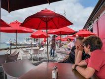 Apreciando a conversação no café da margem de Auckland Bacia do porto do viaduto imagem de stock