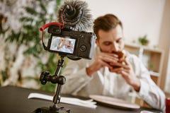 Apreciando o alimento Feche acima da tela da câmara digital com o blogger masculino do alimento que come um sanduíche ao gravar o imagens de stock royalty free