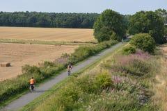 Apreciando o campo, família que dá um ciclo em uma terra do país foto de stock