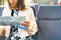 Apreciando o curso Menina nova do sorriso do moderno com a trouxa que viaja pelo trem que senta-se perto da janela que guarda à d fotos de stock royalty free