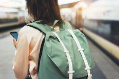 Apreciando o curso Mulher nova do moderno que espera na plataforma da estação com a trouxa no trem bonde do fundo usando o smartp imagem de stock royalty free