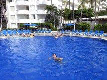 Apreciando a piscina tropical foto de stock