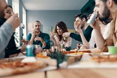 Apreciando a pizza com amigos foto de stock royalty free