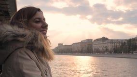 Apreciar a mulher flutua no barco da excursão no rio na cidade na queda ou na mola no por do sol video estoque