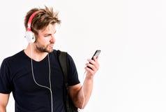 Aprecie fones de ouvido sadios Dispositivo da m?sica Dispositivos acessórios musicais O homem escuta fones de ouvido e smartphone imagem de stock royalty free