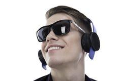 Aprecie a música! Homem novo considerável nos óculos de sol e nos fones de ouvido imagens de stock royalty free